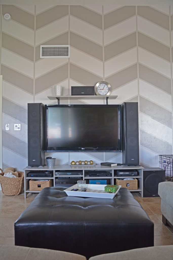 large-flat-screen-tv-against-wall-with-large-scale-painted-herringbone-pattern-in-gray-colors