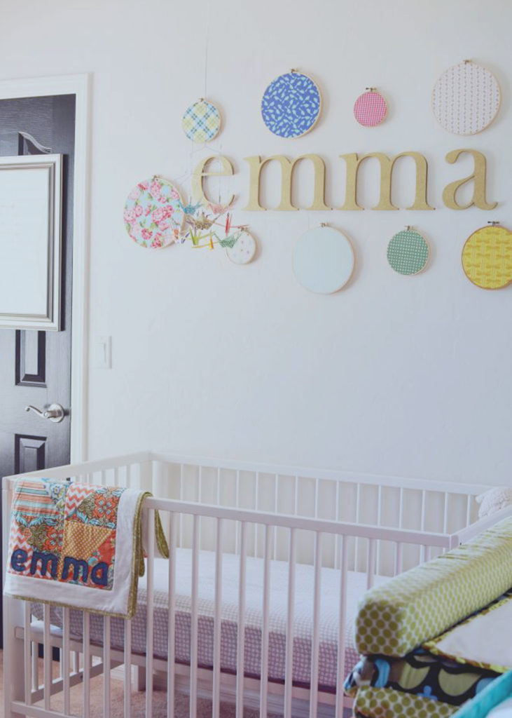 wooden-name-and-fabric-hoop-display-above-crib-in-nursery