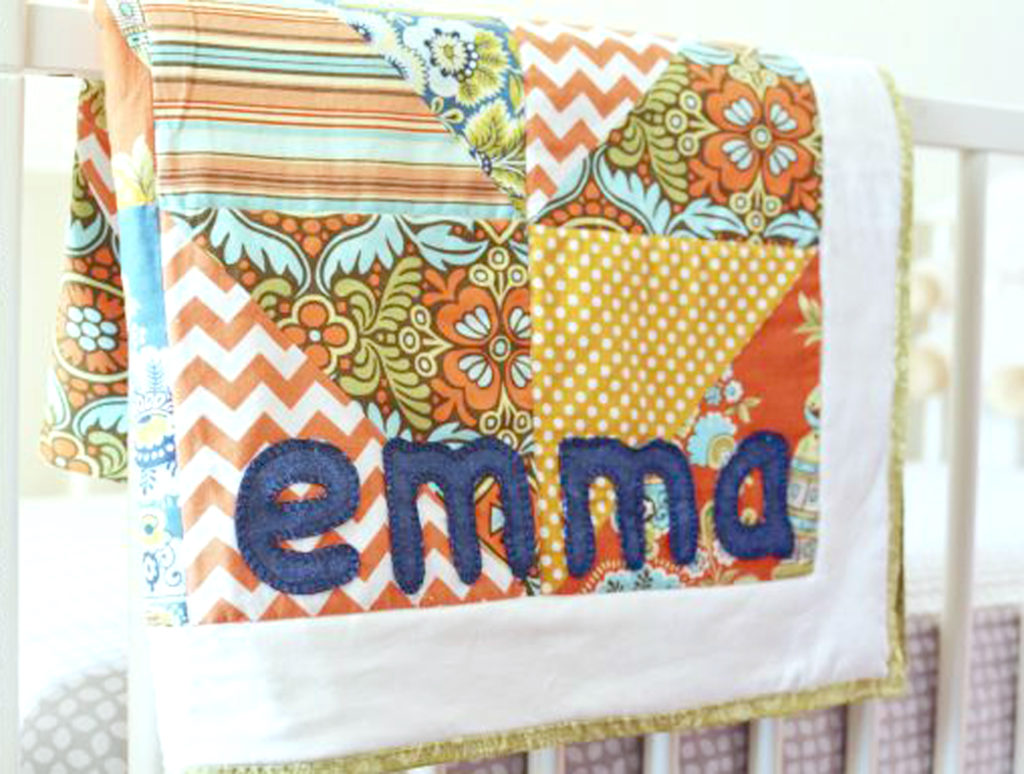 personalized-baby-quilt-hanging-over-crib