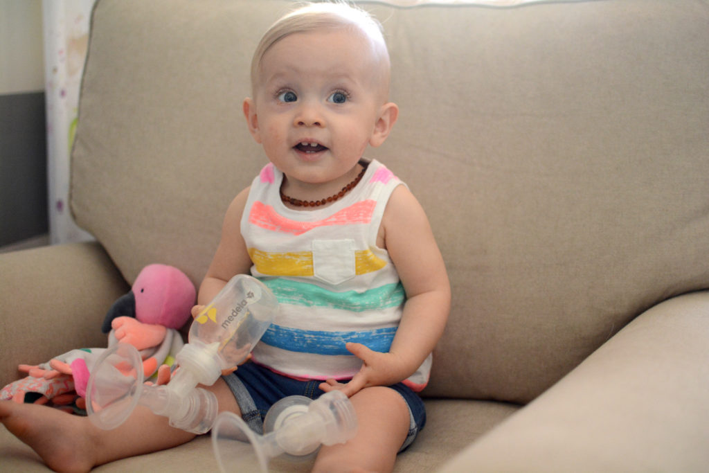 baby-smiling-at-camera-while-playing-with-breast-pump-parts