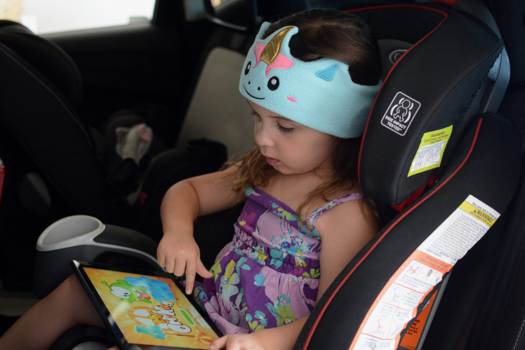 toddler wearing cozyphones headphone while sitting in carseat and playing on a tablet
