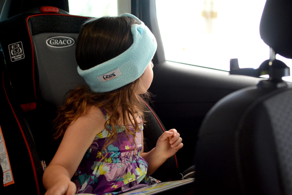 toddler sitting in a carseat wearing cozyphones headphones and looking out the car window