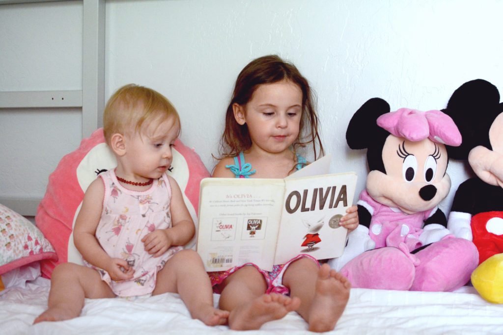 young girl, on a bed, reading a book to the baby girl beside her, surrounded by large stuffed animals
