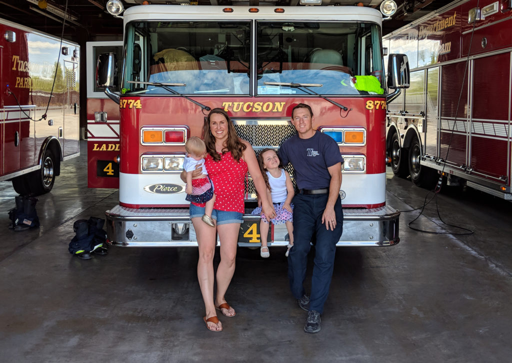 Family standing on front of a fire truck on the fourth of july