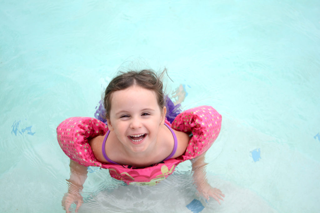 Smiling child in a swimming pool, looking up at the camera