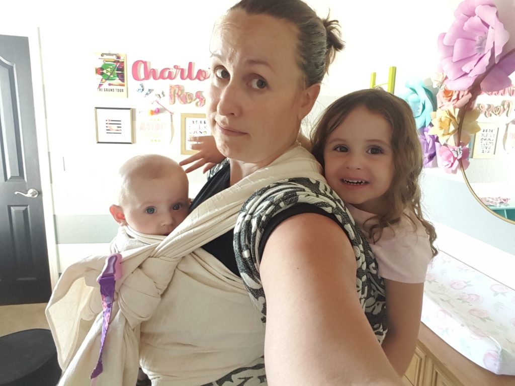 an exhausted mother taking a selfie, wearing an infant wrapped to her front and a toddler girl straped to her back