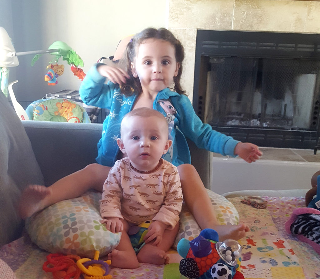 a toddler girl sitting on a boppy pillow behind her infant sister