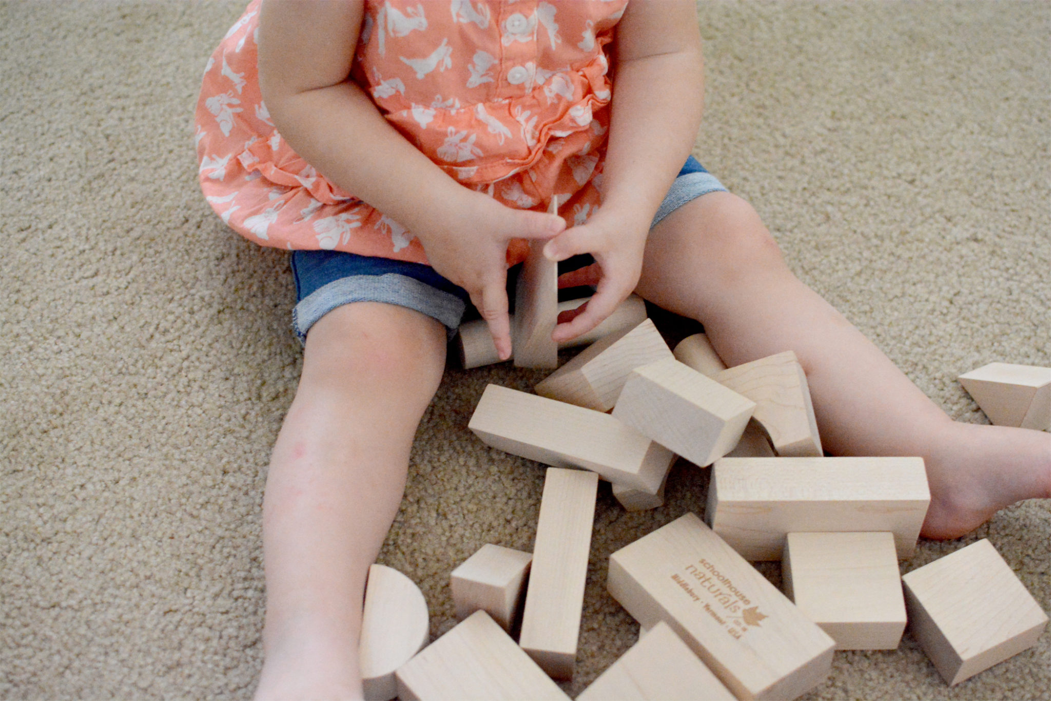 A baby, sitting on a carpeted floor, playing with building blocks