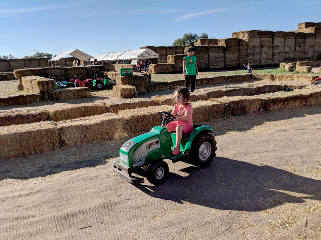 A small girl, driving a small, child-sized motorized, green toy tractor.