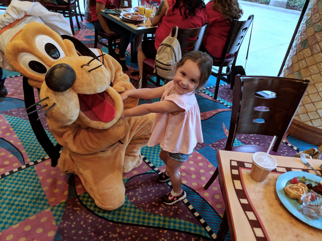 small girl in a pink shirt holding hands with Disney's pluto character and smiling at the camera