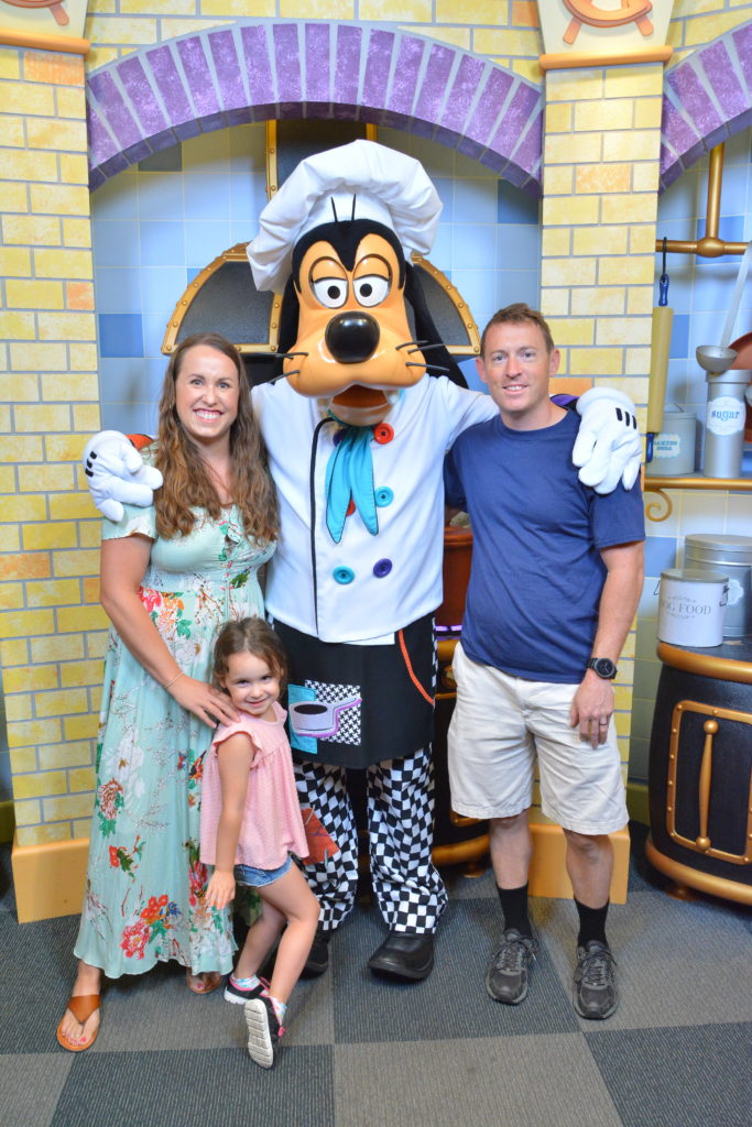 smiling mother, father, and young daughter posing with disney's goofy character