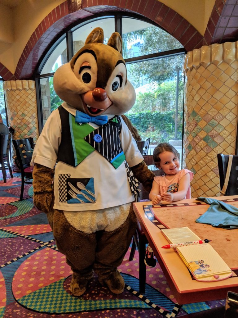 Small girl, in a pink shirt, sitting at a table and smiling while Disney's Dale chipmunk stands next to her