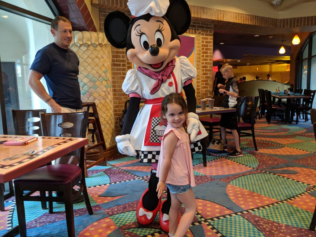 small girl in a pink shirt posing with pastry-chef minnie mouse