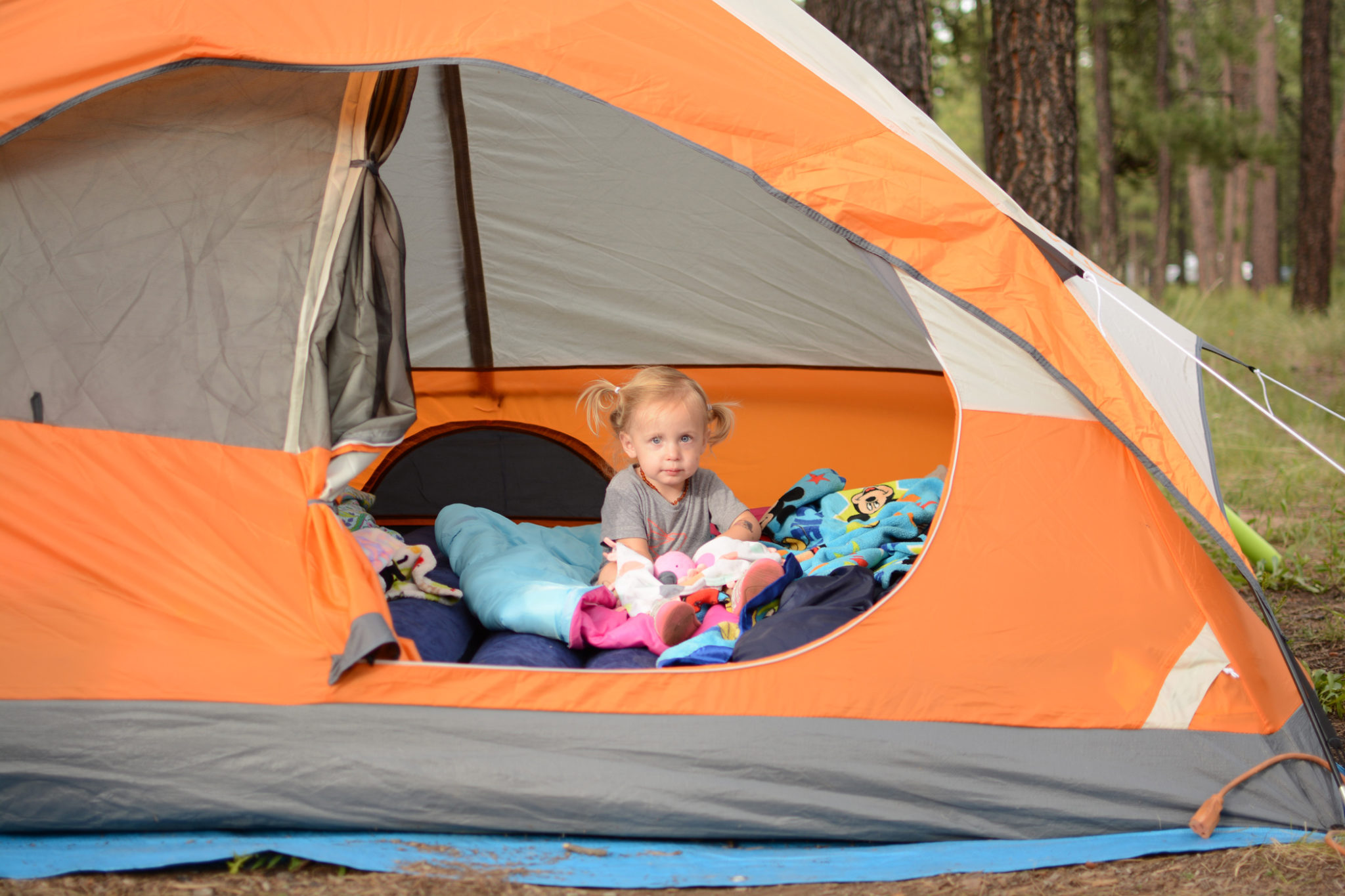 Little girl with blonde pigtails sitting inside an orange tent