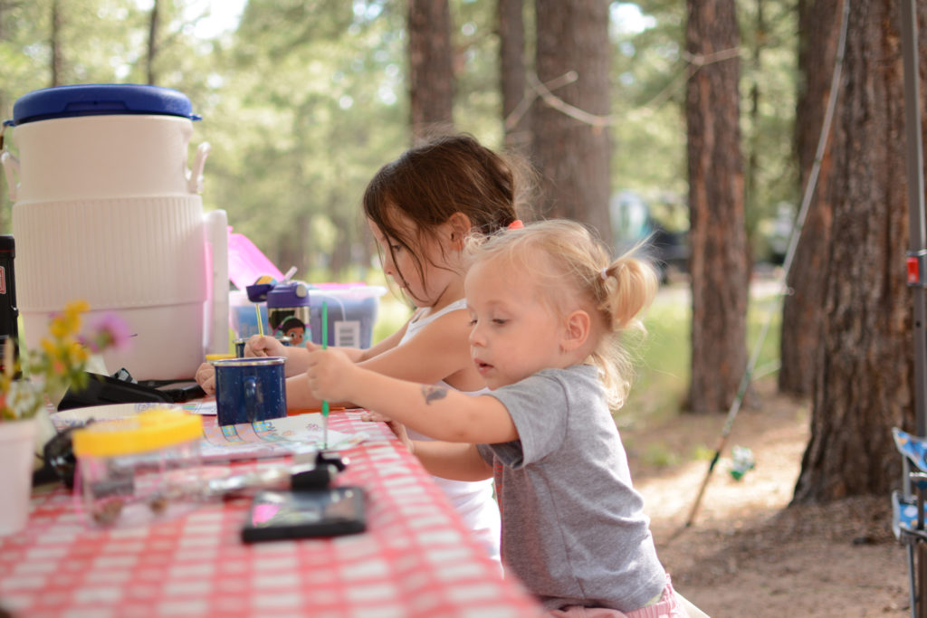 Toddler, siting at a picnic table with her sister, painting