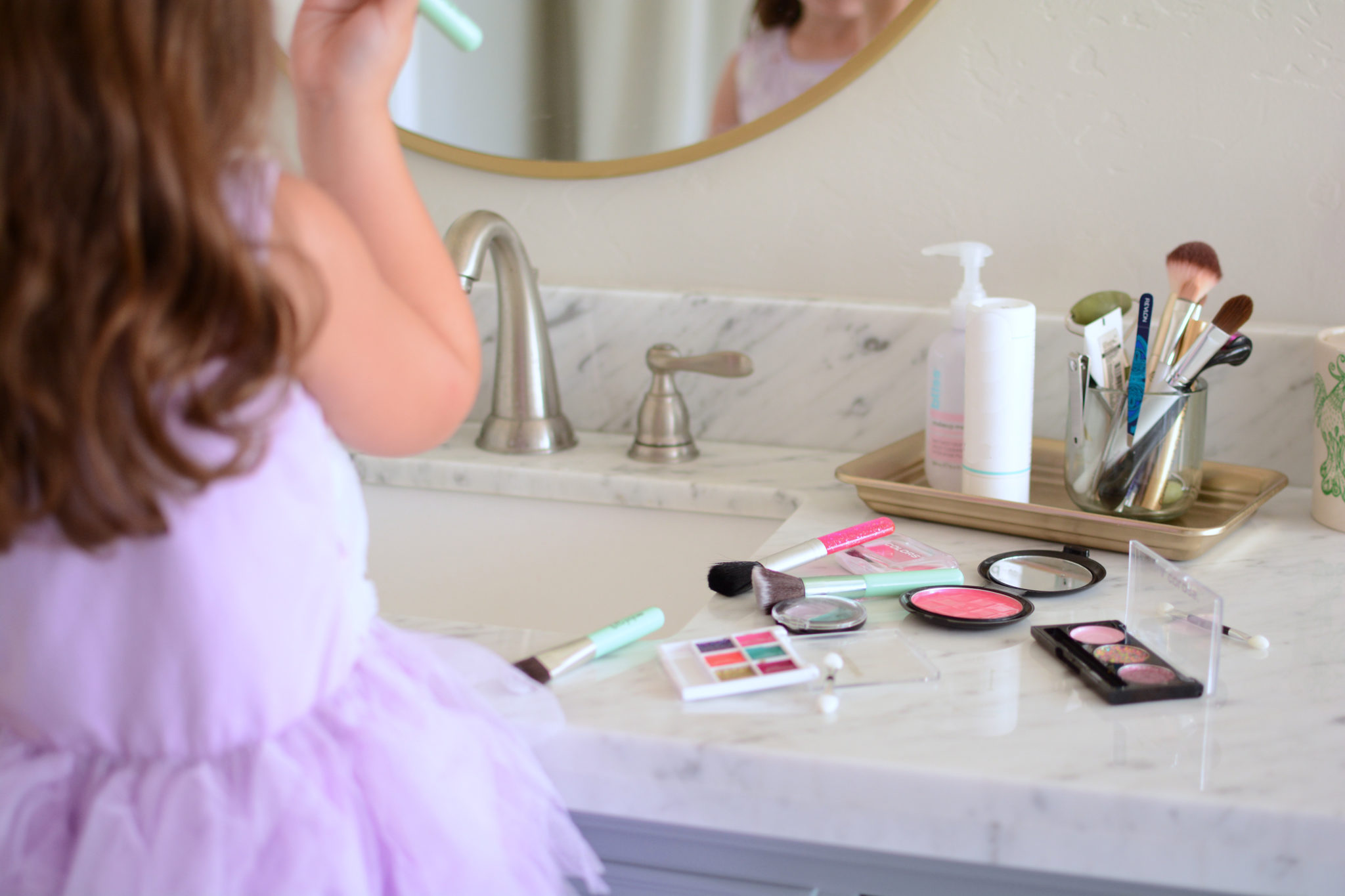 Little girl at bathroom counter, with DIY pretend makeup spread out on the counter next to her