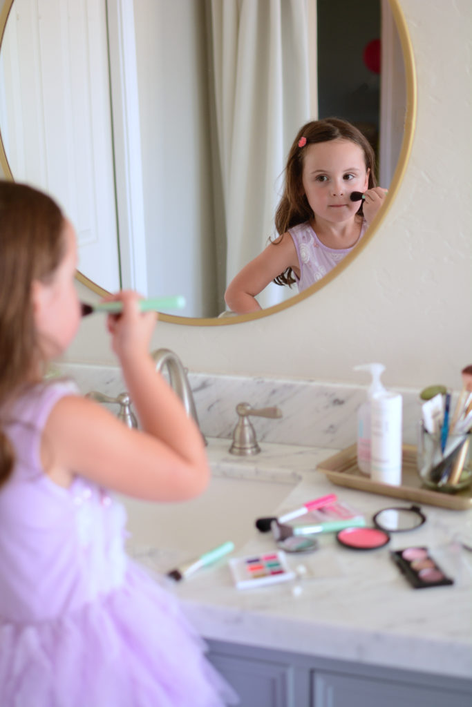 A young girl, in a purple dress, looking in the bathroom mirror, pretending to apply her DIY pretend makeup
