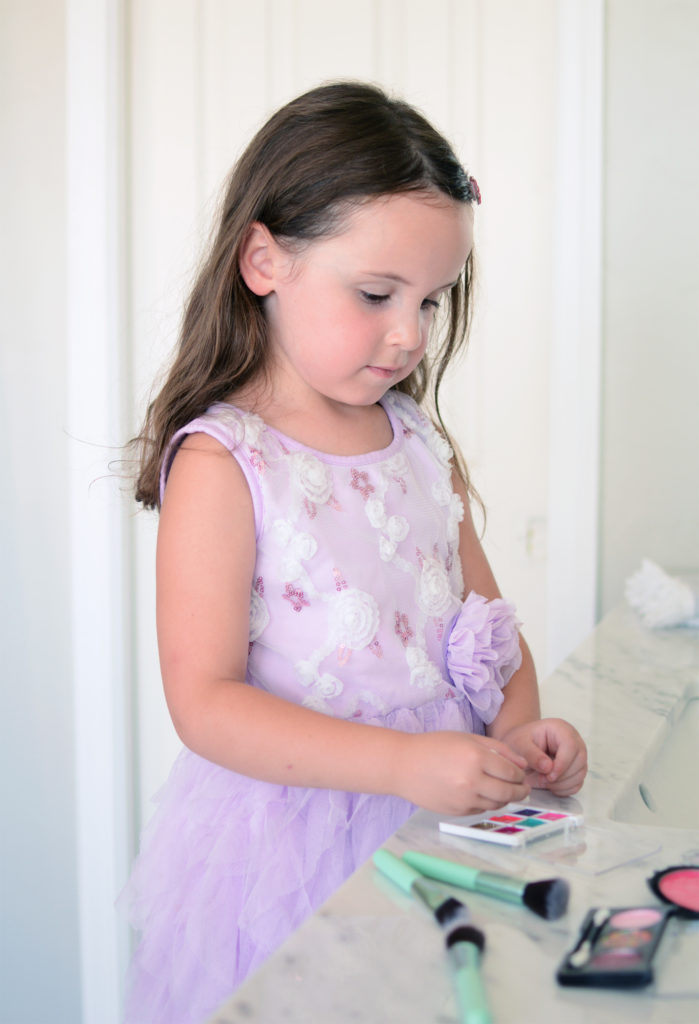 A young girl, in a purple dress, pretending to apply her DIY pretend makeup